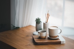 cup of hot coffee and tea on wood table besides window
