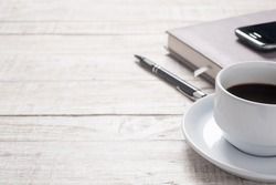 Cup of hot coffee and white note book on wood table background