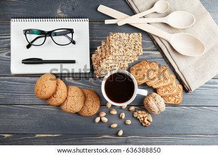 Cup of hot coffee assorted with cookies for breakfast on wooden vintage table. Black glasses on the notes book #636388850