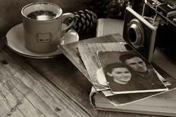 cup of hot coffee next to old photo camera, antique photos and old book on wooden table. black and white style image. selective focus