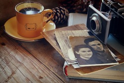 cup of hot coffee next to old photo camera, antique photos and old book on wooden table. vintage filtered image. selective focus