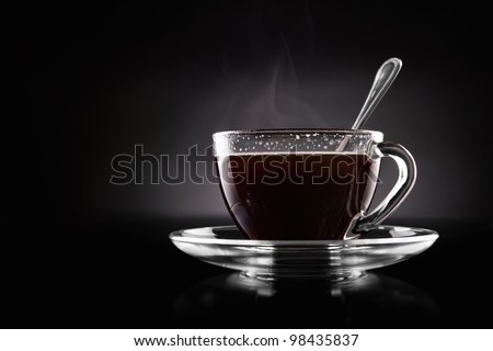 Cup of hot coffee on a black background