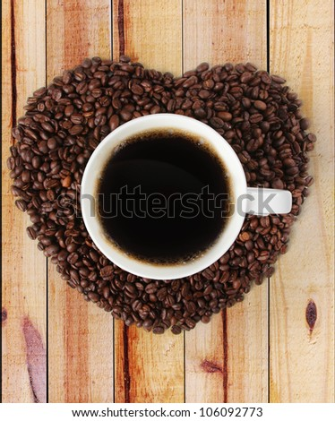 Cup of hot coffee on a Heart shape made from coffee on wood background