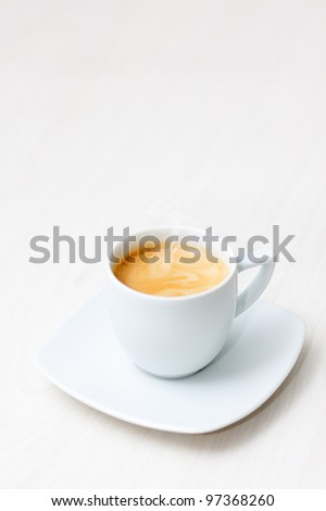 cup of hot coffee on a wooden floor