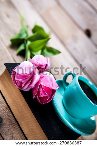 Cup of hot coffee on book with flowers on table on dark background