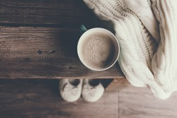 Cup of hot coffee on rustic wooden bench, closeup photo of warm sweater with mug and slippers, winter morning concept, top view