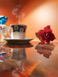 Cup of hot coffee with a pretty red flower with reflection on the table cup of boiling tea with orange background, cup with blue background and yellow flowers
