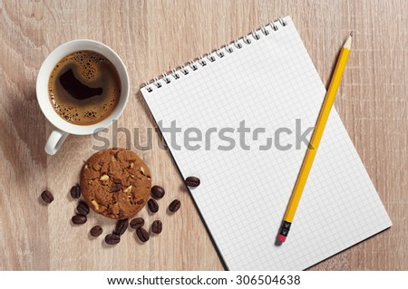 Cup of hot coffee with chocolate cookie and notepad on desk from above