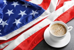 Cup of hot coffee with flag of the USA on dark background