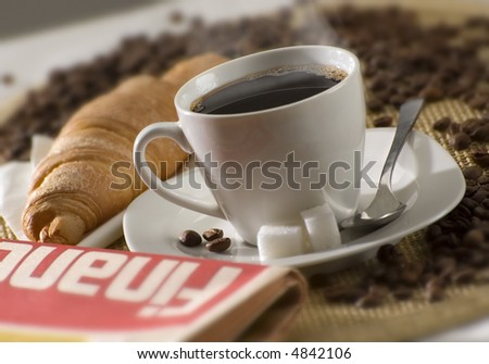 cup of hot coffee with newspaper in the front