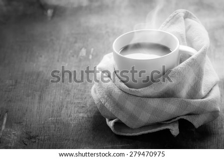 Cup of hot coffee with steam on black and white. Monochrome image.