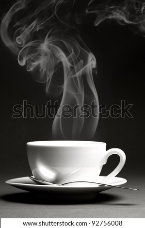 Cup of hot coffee with steam on dark background. Monochrome image.