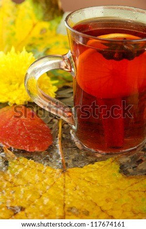 cup of hot drink and autumn leaves, close up