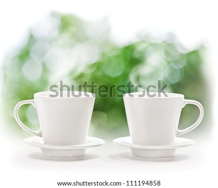Cup of hot drink on summer background