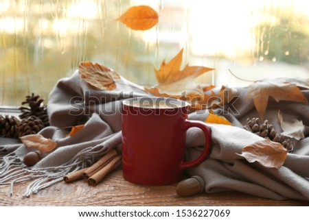 Cup of hot drink, scarf and autumn leaves on windowsill. Cozy atmosphere