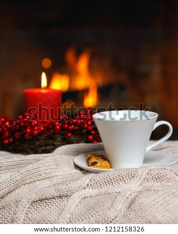 Cup of hot drink with cookie berries and red candle in red Christmas decoration on cozy knitted plaid in front of fireplace. Christmas New Year concept. Cozy relaxed magical atmosphere home interior. #1212158326