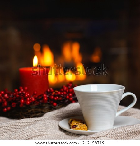 Cup of hot drink with cookie berries and red candle in red Christmas decoration on cozy knitted plaid in front of fireplace. Christmas New Year concept. Cozy relaxed magical atmosphere home interior. #1212158719
