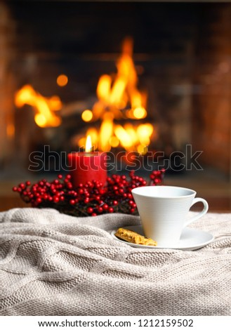 Cup of hot drink with cookie berries and red candle in red Christmas decoration on cozy knitted plaid in front of fireplace. Christmas New Year concept. Cozy relaxed magical atmosphere home interior. #1212159502