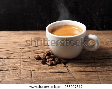 Cup of hot espresso coffee and coffee crop on wood board