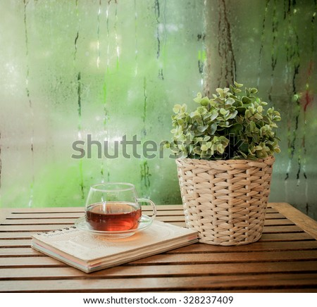 Cup of hot tea and book on a wooden ,water drops on a window glass after the rain.