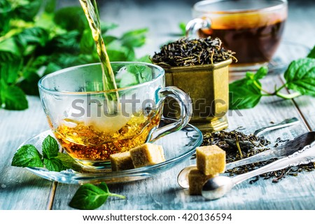 Cup of hot tea cane sugar dry tea leaves and mint herb.