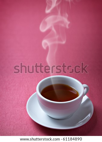 Cup of hot tea on the pink background