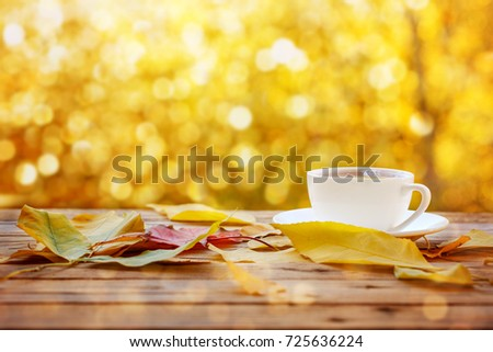 Cup of hot tea or coffee on nature background with yellow leaves. Concept autumn mood.