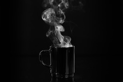 Cup of hot tea or coffee with steam from it in full black color