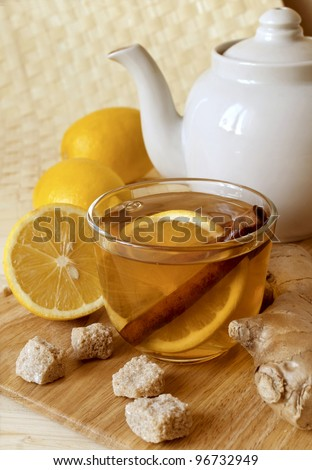 Cup of hot tea with a lemon and ginger on a table