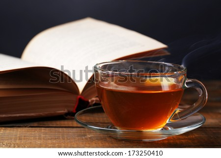 Cup of hot tea with book on table on dark background