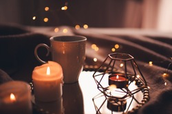 Cup of hot tea with burning candles on tray in bed over Christmas lights close up. Night time atmosphere at home.