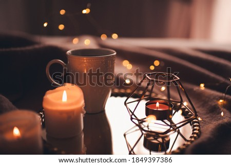 Photo of  Cup of hot tea with burning candles on tray in bed over Christmas lights close up. Night time atmosphere at home.