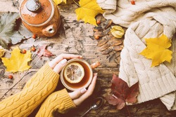 Cup of hot tea with lemon in woman's hands holding it over wooden autumn background with leaves and plaid Top view. Warm drink concept.