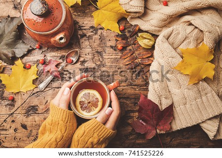 Cup of hot tea with lemon in woman's hands holding it over wooden autumn background with leaves and plaid Top view. Warm drink concept. Photo stock ©