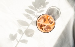 Cup of ice coffee with milk in white bed. Cold brew coffee. Flatlay, top view. Minimalism. Morning with sunlight.
