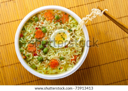 Cup of instant noodles with vegetables on a traditional mat