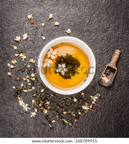 Cup of Jasmine tea, old wooden scoop and fresh flowers on dark stone background, top view #268789955