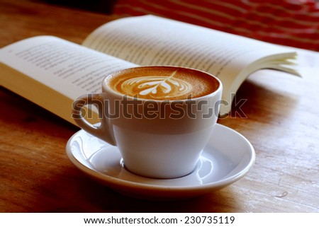 cup of latte or cappuccino coffee with a book in coffee shop with vintage retro filter effect
