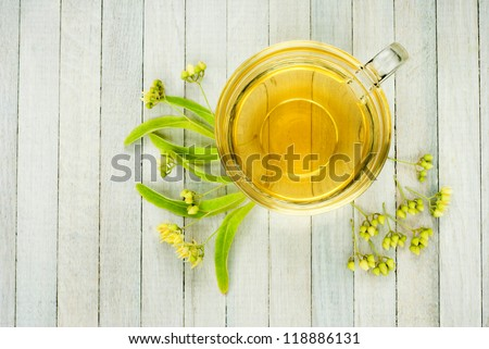cup of lime tree tea and linden blossoms, bright wooden, directly above
