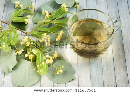 cup of lime tree tea and linden blossoms, bright wooden table