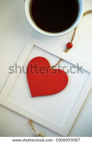 Cup of love, coffee with red heart. Red heart on a rope in the wooden frame. Valentine's day. Morning. The 14th of February. #1006093087