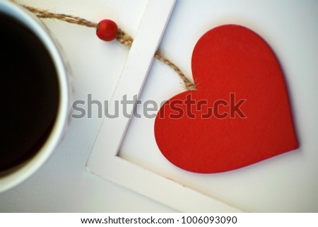 Cup of love, coffee with red heart. Red heart on a rope in the wooden frame. Valentine's day. Morning. The 14th of February. #1006093090