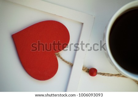 Cup of love, coffee with red heart. Red heart on a rope in the wooden frame. Valentine's day. Morning. The 14th of February. #1006093093