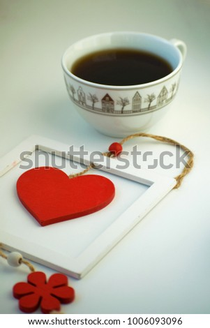 Cup of love, coffee with red heart. Red heart on a rope in the wooden frame. Valentine's day. Morning. The 14th of February. #1006093096