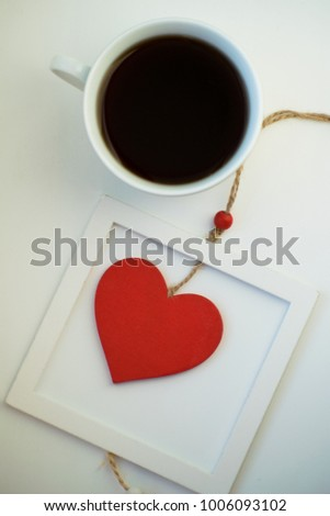 Cup of love, coffee with red heart. Red heart on a rope in the wooden frame. Valentine's day. Morning. The 14th of February. #1006093102