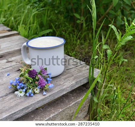 Cup of milk with bunch of wildflowers on old wooden table over grass background, summer rural still life