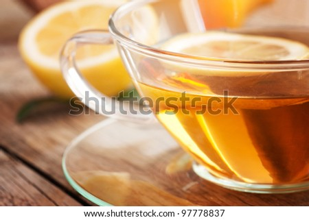 Cup of organic  lemon fruit tea on nature wooden background