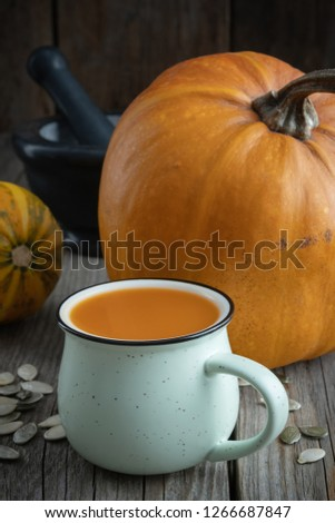 Cup of pumpkin juice, pumpkins and black mortar on wooden table.