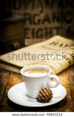 Cup of rich milky coffee with a chocolate bonbon on the saucer and a folded newspaper on the table behind in a coffee break concept