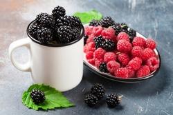 Cup of ripe blackberries and raspberries on stone table